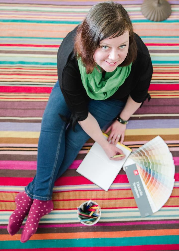Nainen istuu värikkäällä matolla